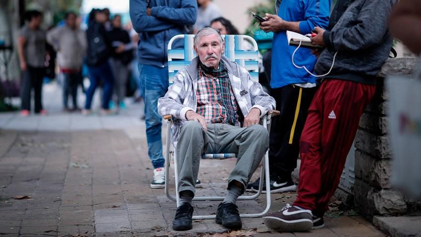 Adultos mayores esperan en fila para poder cobrar su jubilación en un Banco de San Justo, en la provincia de Buenos Aires.