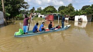 Un grupo de cinco personas rescata sus pertenencias a bordo de una canoa
