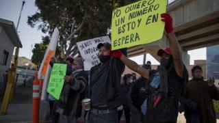 Migrantes en la frontera entre San Diego y Tijuana con letrero yo quiero un número estoy en espera