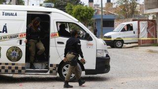 Policías resguardan una finca donde hallaron una fosa clandestina, en Jalisco