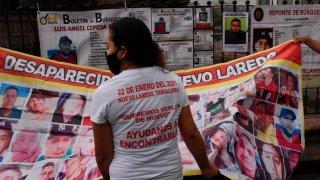 Mujer frente a una manta impresa con el rostro de desaparecidos en la frontera norte de México