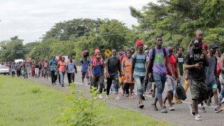Grupo de personas migrantes, en su mayoría de Haití, caminan por una carrera del sureste de México